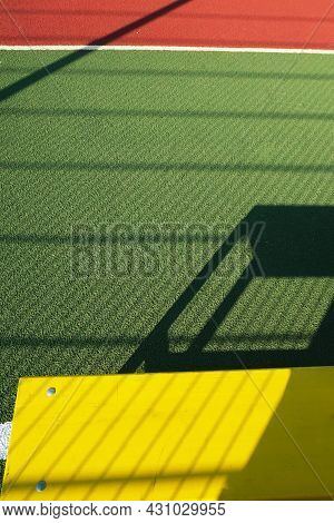Outdoor Sport Playground With Rubberized Ground. Yellow Bench On A Green Sport Field. Physical Cultu