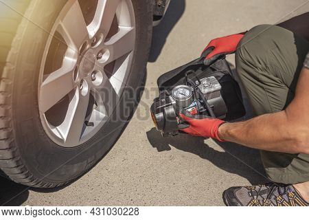 Male Hands In Glove And Portable Tire Pump For Inflating Auto Wheel. Tyre Inflator Air Compressor Wi