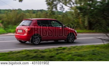 Skoda Fabia Mk2 Second Generation 5j In Motion On The Country Road. Red Car Driving Fast On The Rura