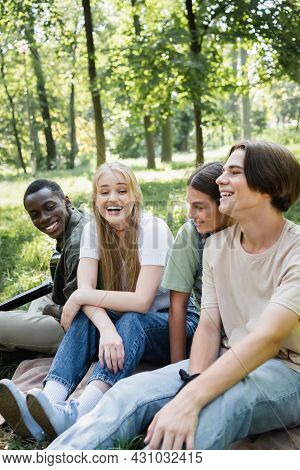 Cheerful Teen Friends Sitting Near African American Boy With Acoustic Guitar In Park