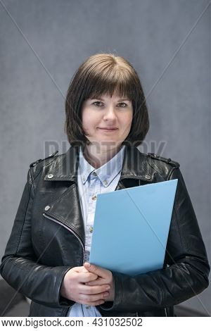 Young Woman Inspector In Leather Jacket With Documents In Hands. Modern Business Woman. Informal Rec
