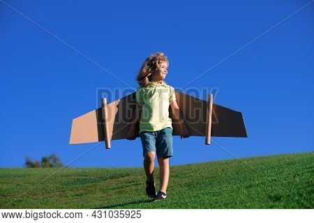 Kids Fly. Funny Child Boy Pilot Flying With Toy Cardboard Airplane Wings On Blue Sky, Copy Space. St