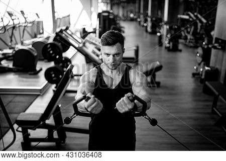 Strong Sporty Man Training Hard In The Gym. Bodybuilding Muscle Man Working Out.