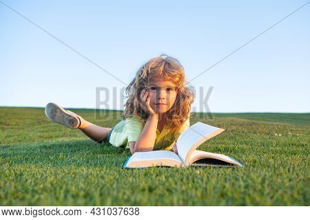 Funny Kid Reading The Book In Spring Park. Child Boy Is Reading A Book On The Spring Park. Relaxing