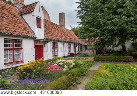 Brugge, Flanders, Belgium - August 4, 2021: House Row And Garden With Flowers As Courtyard Of Rooms