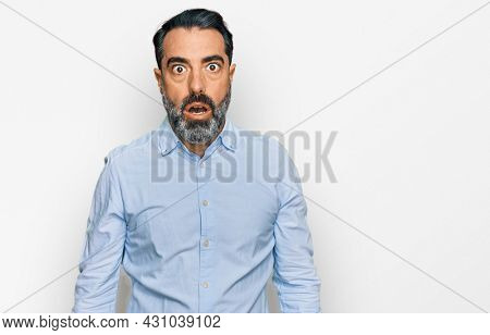 Middle aged man with beard wearing business shirt afraid and shocked with surprise and amazed expression, fear and excited face.