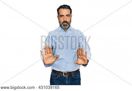 Middle aged man with beard wearing business shirt moving away hands palms showing refusal and denial with afraid and disgusting expression. stop and forbidden.