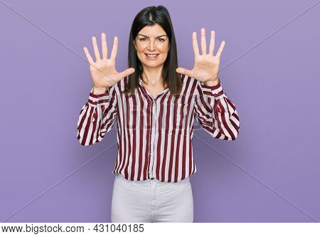Beautiful brunette woman wearing striped shirt showing and pointing up with fingers number ten while smiling confident and happy.