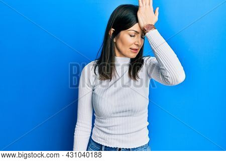 Young hispanic woman wearing casual clothes surprised with hand on head for mistake, remember error. forgot, bad memory concept.