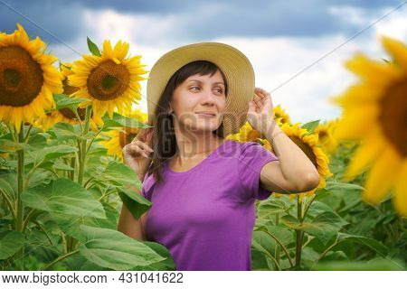 Woman in sunflower field at day. Nature and people.