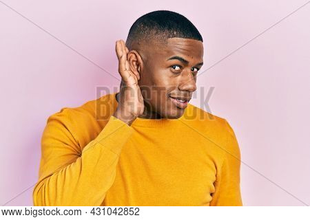 Young black man wearing casual yellow sweater smiling with hand over ear listening and hearing to rumor or gossip. deafness concept.