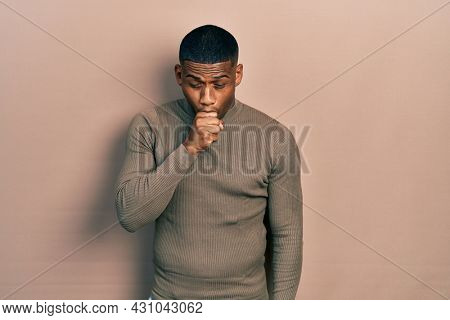 Young black man wearing casual turtleneck sweater feeling unwell and coughing as symptom for cold or bronchitis. health care concept.