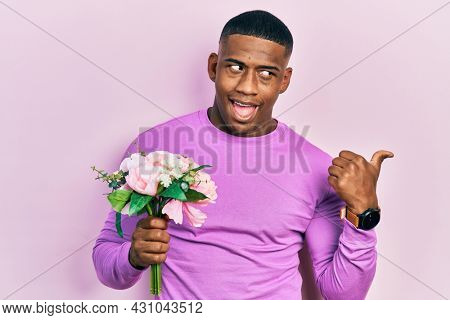 Young black man holding bouquet of white flowers pointing thumb up to the side smiling happy with open mouth