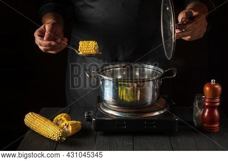 A Professional Chef Cooks Corn. Close-up Of A Cook Is A Hand While Cooking In A Restaurant Kitchen