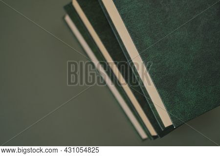 Knowledge And Education. Books Stack With Green Covers On A Dark Green Background. Business Literatu