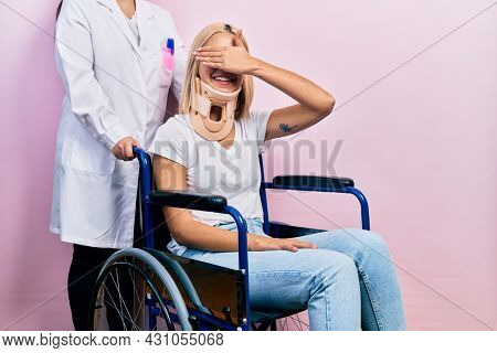 Beautiful blonde woman sitting on wheelchair with collar neck smiling and laughing with hand on face covering eyes for surprise. blind concept.