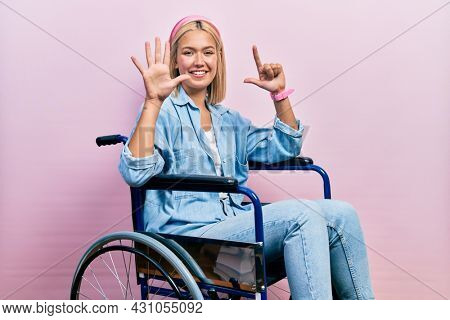 Beautiful blonde woman sitting on wheelchair showing and pointing up with fingers number seven while smiling confident and happy.