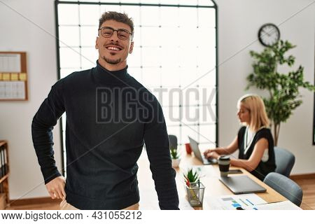 Two business workers smiling happy working. Man standing at the office.