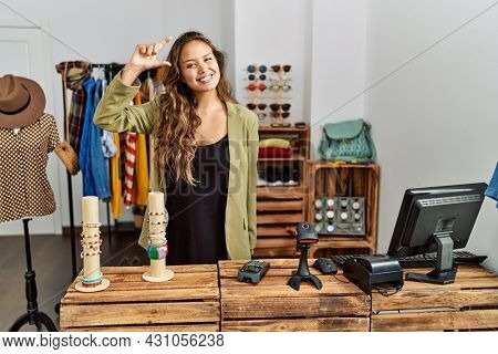 Beautiful hispanic woman working at fashion shop smiling and confident gesturing with hand doing small size sign with fingers looking and the camera. measure concept.