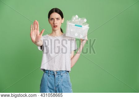 Young frowning woman carrying a plastic container full with empty recyclable plastic. Recycling concept showing stop gesture