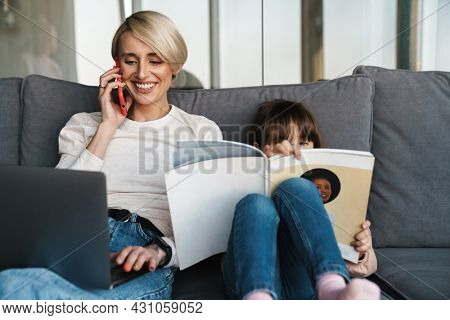 Happy young mother and her little daughter sitting on a couch with laptop computer, looking at screen, on a video call or watching movies, woman talking on mobile phone