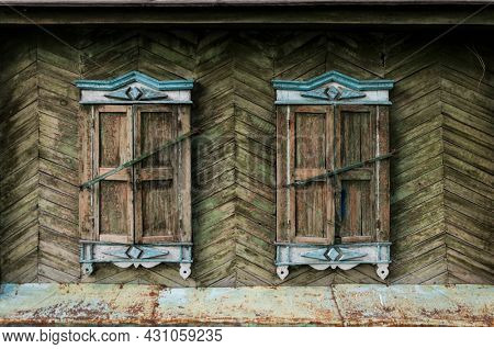 Two windows in old wall with closed shutters. Facade of ancient house. Windows with closed old wooden shutters.