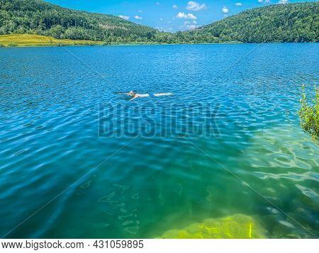 One unrecognizable person swim in the Narlay lake, Le Frasnois, Bourgogne-Franche-Comté, Jura