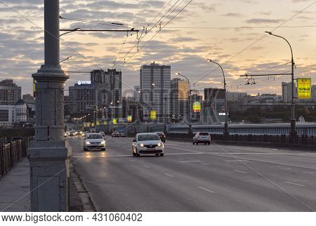 Novosibirsk, Siberia, Russia - 10.10.2019: Cars With Headlights On Go On The October Bridge Over The