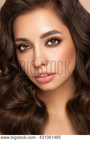 Brunette Girl With Perfect Makeup. Smiling Beautiful Model Woman With Long Curly Hairstyle. Care And