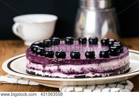 Side View Of Delicious Homemade Blueberry Cheesecake Garnished With Preserved Blueberry In Brown Cer