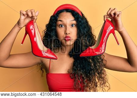 Young latin woman holding red high heel shoes puffing cheeks with funny face. mouth inflated with air, catching air.