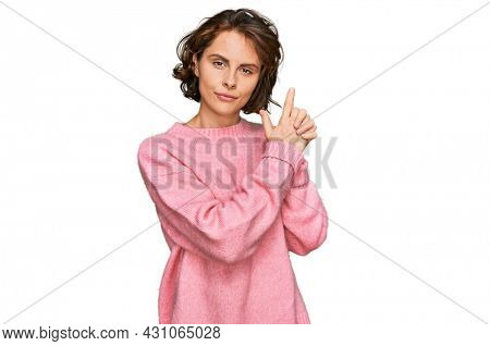 Young hispanic woman wearing casual clothes holding symbolic gun with hand gesture, playing killing shooting weapons, angry face