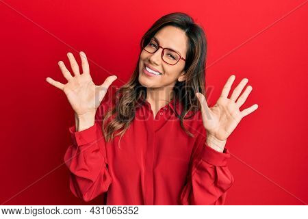 Young latin woman wearing casual clothes and glasses showing and pointing up with fingers number ten while smiling confident and happy.