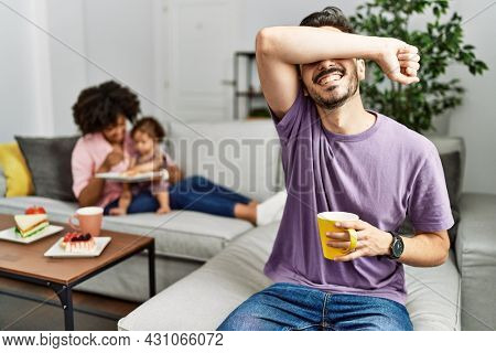 Hispanic father of interracial family drinking a cup coffee smiling cheerful playing peek a boo with hands showing face. surprised and exited