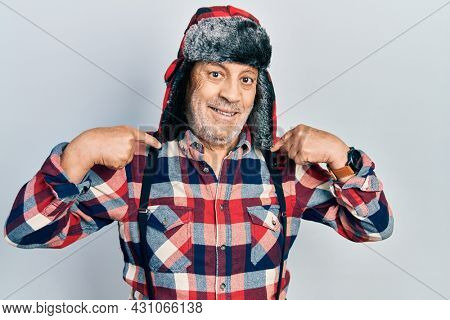 Handsome mature man wearing winter hat with ear flaps looking confident with smile on face, pointing oneself with fingers proud and happy.