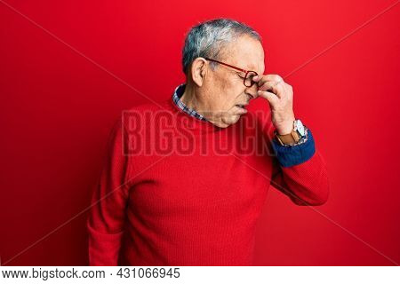 Handsome senior man with grey hair wearing casual clothes and glasses tired rubbing nose and eyes feeling fatigue and headache. stress and frustration concept.