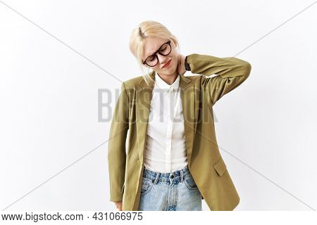 Beautiful caucasian business woman standing over isolated background suffering of neck ache injury, touching neck with hand, muscular pain
