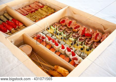 Box With Sandwiches, Eclairs, Bruschetta With Cold Cuts, Cheese And Seafood. Gourmet Snack Food In C