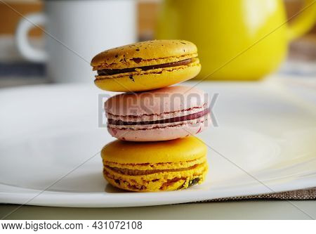 Yellow And Pink Mango And Passionfruit, Salted Caramel, Raspberry Macaroons On White Plate