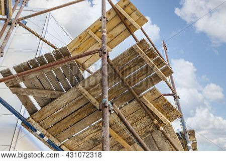 Scaffolding And Scaffolding With Wooden Decks, Against A Blue Sky. Performing Construction Work At H