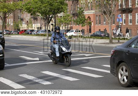 Bronx, New York/usa - May 18, 2020: Helmet And Mask Wearing Man Rides Street On Motorcycle.