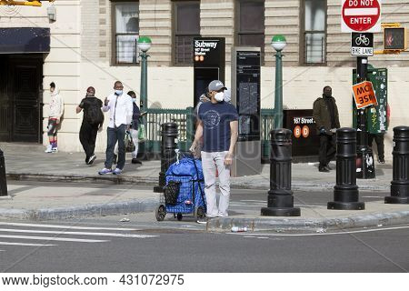 Bronx, New York/usa - May 18, 2020: Man Wearing Mask Prepares To Cross Street With His Laundry.