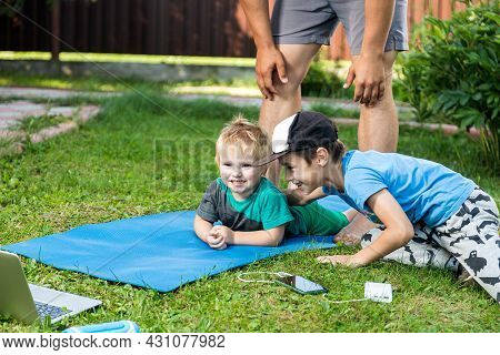 Two Cheerful Boy Brothers Of Different Ages Play Fun, Sit On The Grass On A Warm Summer Day. The Con