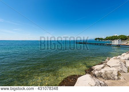 Beautiful Beach With A Small Empty Wooden Pier On Lake Garda (lago Di Garda) In Front Of The Small V