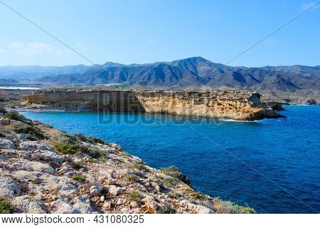 a panoramic view over the reefs of Cala Blanca beach, in Lorca, in the Costa Calida coast, Region of Murcia, Spain, highlighting the Calnegre mountain range in the background