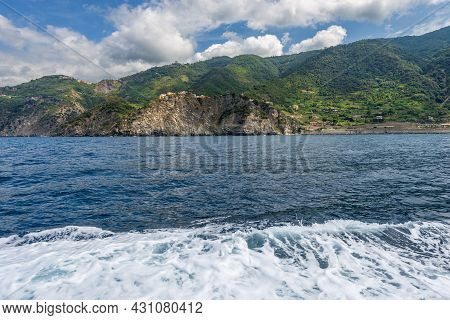 Coast Of The Cinque Terre Seen From The Sea With The Corniglia Village On The Cliffs, National Park
