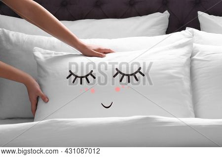 Woman Plumping Pillow With Cute Face In Bedroom, Closeup