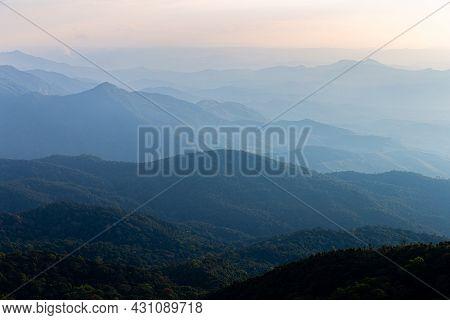 Natural Scene Of Hazy Blue Mountain Range Of Tropical Rainforest At Sunrise.