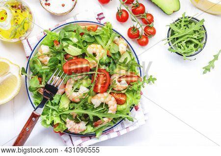 Shrimp Salad With Cherry Tomatoes, Arugula, Avocado, And Oil Lemon Dressing On White Background. Top