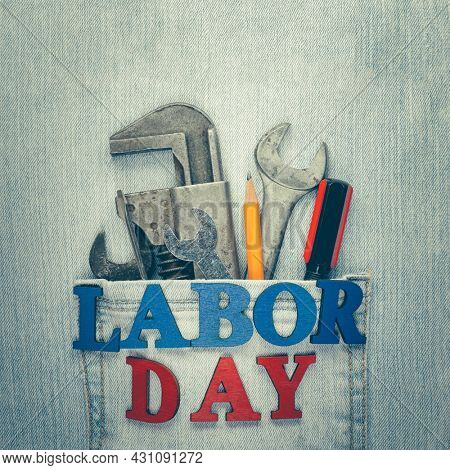 Worn and weathered blue jeans with work tools in the pocket and Labor Day text, celebrating American workers.